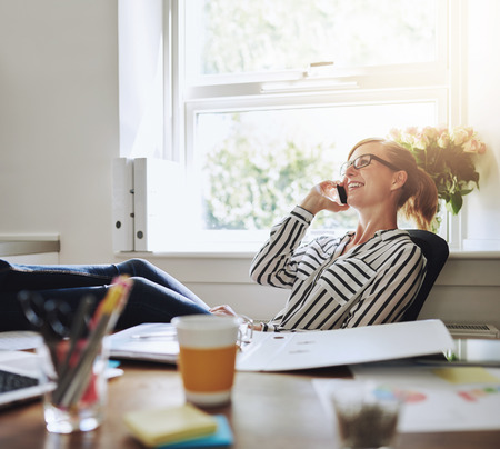 Happy Young Businesswoman Talking to Someone on her Mobile Phone While Relaxing Inside the Office with Legs on her Desk.