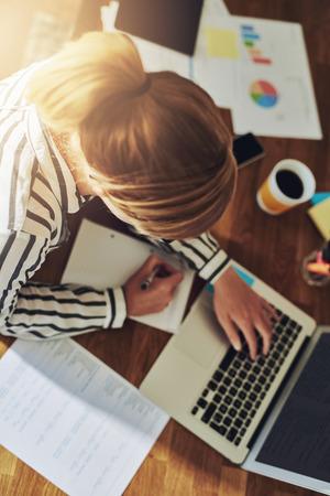 research: Trabajador mujer empresaria exitosa trabajando en su escritorio en su redacción de notas de oficina en casa mientras se investiga nuevos mercados en el equipo, vista aérea Foto de archivo