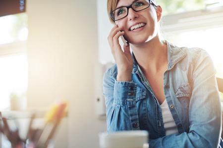 amigas conversando: Close up Joven Oficina Mujer hablando con alguien por su teléfono móvil mientras mira en la distancia con feliz expresión facial.