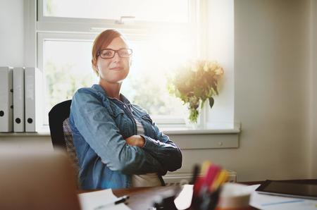 Zekere Jonge kantoor vrouw zit op haar bureau met armen Crossing over haar buik, lachend naar de camera tegen de glazen ruit van het Bureau.