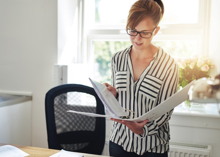 attractive female: Young business woman standing in her home office reading notes in an office binder backlit by the glow of the sun through the window