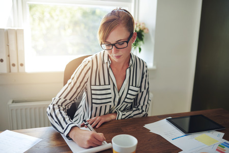 stylish women: Attractive stylish businesswoman wearing glasses sitting at her desk taking notes while talking on her mobile phone taking a clients call