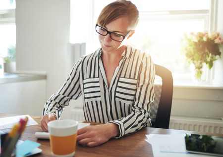 hardworking: Successful female entrepreneur working at home from her office sitting at her desk taking notes or writing new ideas for a business strategy