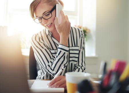 persona escribiendo: Mujer joven autónomos acertado que trabaja desde una oficina en casa tomando un pedido por teléfono móvil a partir de productos en su sitio web y escribirlo en una libreta