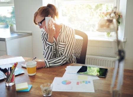 Jovem gestora trabalhando em sua mesa no escritório tendo uma chamada em seu telefone celular enquanto escrevia notas em um bloco de notas, tabelas e gráficos em primeiro plano