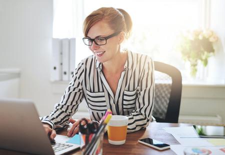 mujeres sentadas: Sonriente mujer empresaria trabajando en su e-negocios sentado en su oficina en casa, navegar por internet en su computadora portátil con una sonrisa