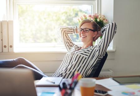 Glücklich zufrieden Geschäftsfrau in ihrem Stuhl sich entspannt im Büro mit den Händen hinter dem Hals und einem Lächeln der Zufriedenheit und Zufriedenheit an ihrem Erfolg Standard-Bild - 45163943