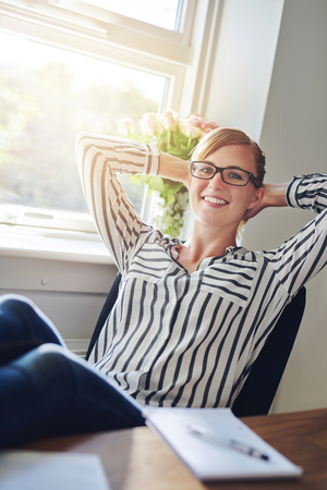 Relaxed confident successful businesswoman or female entrepreneur reclining back in her chair at her desk with her hands behind her neck and beaming smile of satisfaction photo