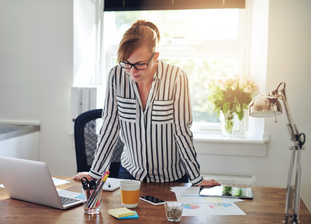 Concerned businesswoman studying information on the screen of her laptop computer as she stands leaning on her desk in the office in front of a bright window photo