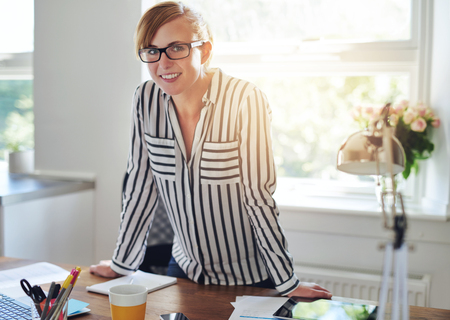 Pretty attractive female entrepreneur standing in her home office leaning on her desk smiling at the camera in front of a window with sun flare