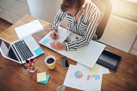 contabilidad: Joven empresaria trabajando duro en su escritorio escribiendo notas en un bloc de su ordenador portátil con gráficos analíticos y gráficos en frente de ella, opinión de alto ángulo Foto de archivo