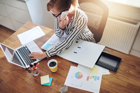 mujeres trabajando: El �xito de negocios con un e-negocio trabajando desde una oficina en telemarketing casa y tomar pedidos por tel�fono o consultar con los clientes, opini�n de alto �ngulo