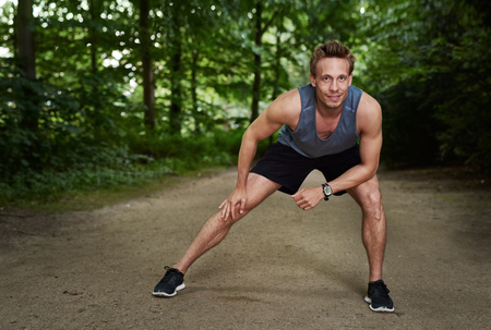 limbering: Athletic Handsome Man Doing Warm Up Stretching for an Outdoor Running Exercise at the Park Stock Photo