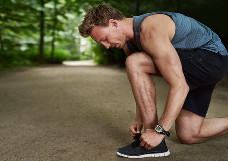 man working out: Side View of a Fit Handsome Young Man Tying Shoelace While Doing an Outdoor Exercise at the Park.