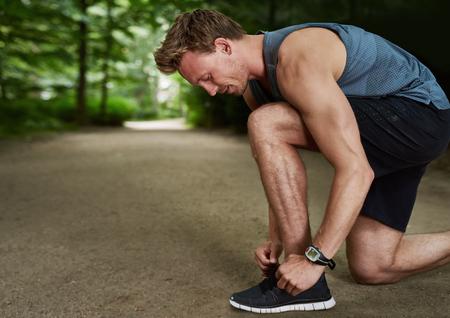 sportsman: Vista lateral de un Fit Hombre joven hermoso que ata el cordón Aunque haciendo un ejercicio al aire libre en el Parque.