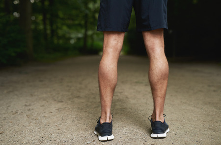 the guy: Tone Calf Muscle of a Fit Young Guy Standing at the Park and Facing Backwards.
