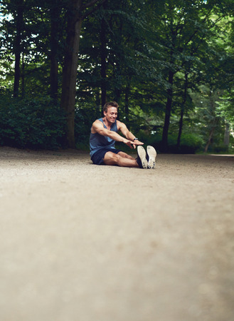 limbering: Athletic Young Man Sitting on the Ground at the Park and Reaching his Toes for his Warm Up Exercise.