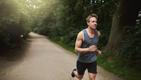 actividades recreativas: Toma tres cuartos de un Hombre joven atlético haciendo un ejercicio de correr al aire libre en el parque