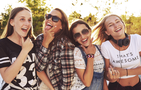 teenagers laughing: Group of girls making fun expressions a the camera, outside in a park Stock Photo