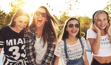 escuchando musica: El grupo de adolescentes riendo en voz alta el día de s del verano Foto de archivo
