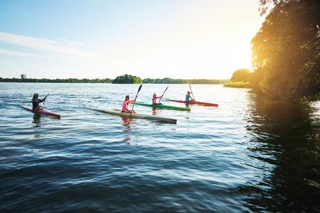 Team of sports kayaks racing on the lake