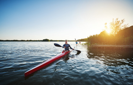 rower: Woman kayaking on a lake while the sun setting