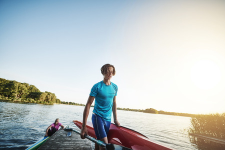 fibreglass: Young man carrying a kayak after getting out of the water Stock Photo