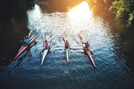 recreational sport: Team of rowing people sailing against camera in sunset