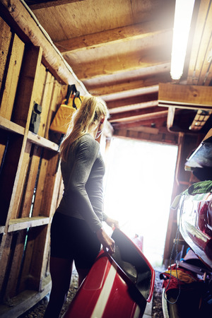 hobby hut: Athletic woman carrying a kayak from the boathouse Stock Photo