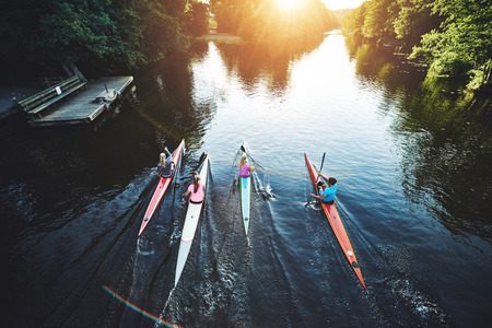 Team of rowing people racing in the sunset