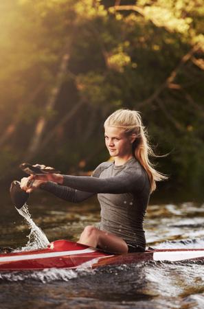 kayaker: Athletic elite kayaker racing on the water