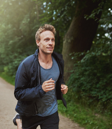 men running: Three Quarter Shot of a Physical Fit Man Running at the Park Early in the Morning with Happy Facial Expression. Stock Photo