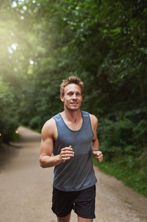 three quarter: Three Quarter Shot of an Athletic Young Man Running at the Park in the Morning. Stock Photo