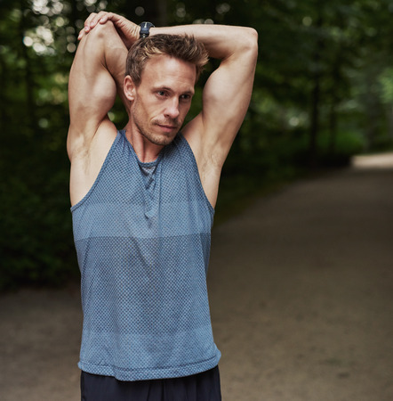 limbering: Half Body Shot of a Handsome Athletic Man Stretching his Arms Behind his Head at the Park. Stock Photo