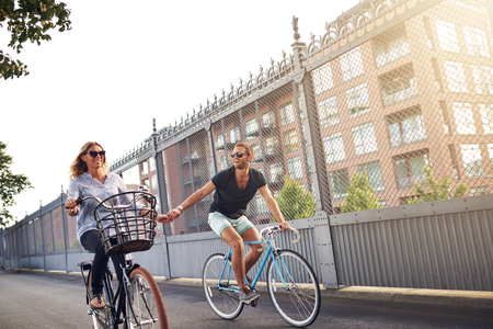 urban transport: Romantic couple holding hands as they go cycling riding their bikes down an urban street past apartment blocks