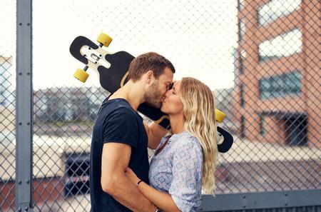 baiser amoureux: Beau couple embrassant tout en se tenant dans un parc de la ville