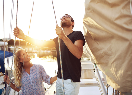 man looking: Couple on Their Sail Boat Checking it Before heading out