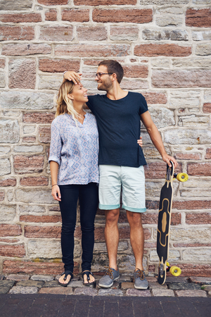 endearment: Humorous couple loving each other standing against wall Stock Photo