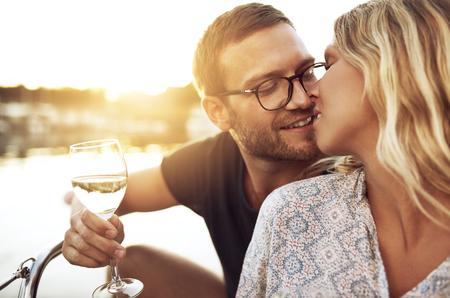 enamorados besandose: Pares que se besan suavemente mientras disfruta de una copa de vino