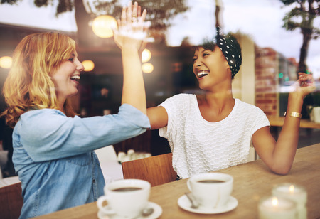 congratulation: Happy exuberant young girl friends giving a high five slapping each others hand in congratulations as they sit together in a cafeteria enjoying a cup of hot coffee, multi ethnic viewed through glass