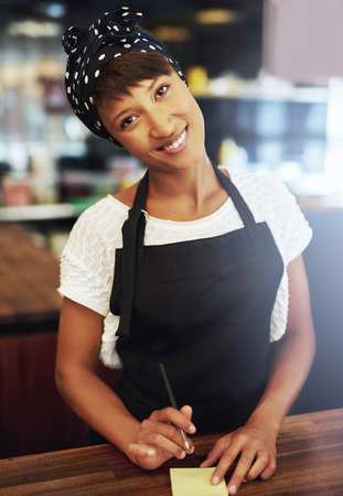 enterprising: Sincere attractive young female African American coffee shop owner standing in an apron and bandanna behind the counter giving the camera a lovely warm smile