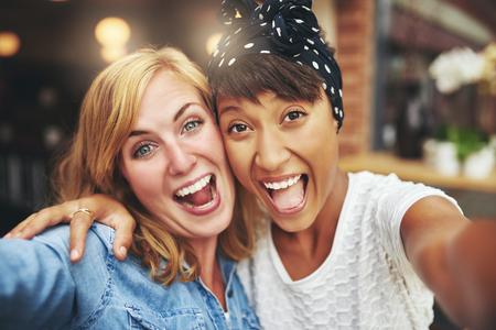 Exuberant gelukkig multi-etnische meisje vrienden genieten van een hartelijke lach als ze het gezicht van de camera arm in arm in een koffieshop, met kop en schouders