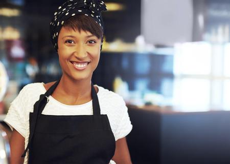 El éxito de joven empresario afroamericano de pie en su tienda de café en un delantal y un pañuelo sonriendo a la cámara