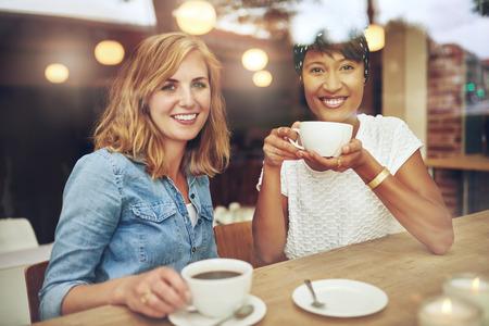Jóvenes de varios amigos femeninos étnicos atractivos sentados juntos disfrutando de café en una mesa en una sonrisa cafetería felizmente a la cámara, vistos a través del cristal con reflejos