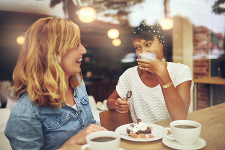 Two good female friends enjoying a cup of coffee together in a coffee house with one laughing as the other makes a gesture of embarrassment, multi ethnic young ladies Фото со стока