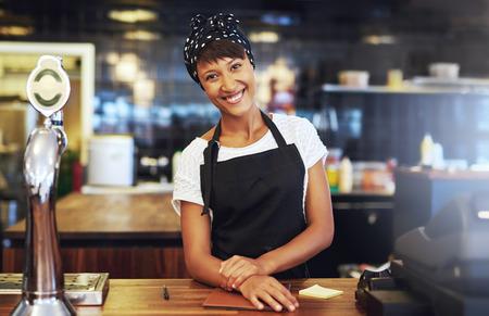 delantal: C�lida bienvenida empresario joven de pie detr�s del mostrador en su cafeter�a que da a la c�mara una radiante sonrisa de bienvenida Foto de archivo