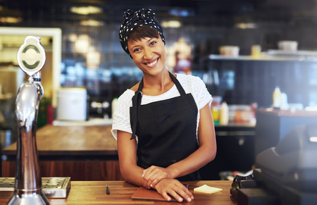 Warm welcoming young business entrepreneur standing behind the counter in her cafe giving the camera a beaming smile of welcome