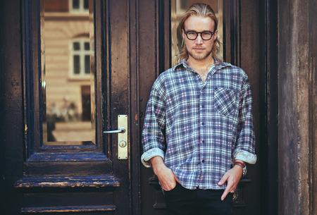 capelli lunghi: Ritratto di un giovane uomo serio intelligente piedi contro la costruzione. Lunghi capelli biondi