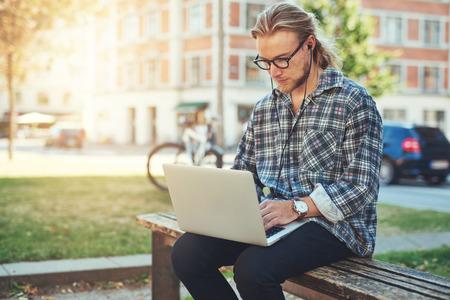banc de parc: Entrepreneur travail idée sur son ordinateur portable. ville style de vie