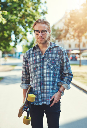 man with long hair: Portrait of cool young man with long hair and glasses carrying a skateboard